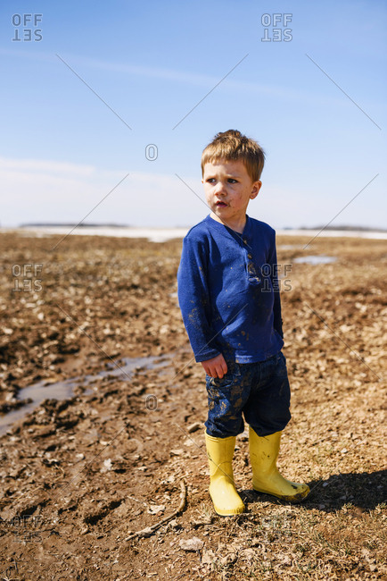 A  young boy playing in mud puddles in a field