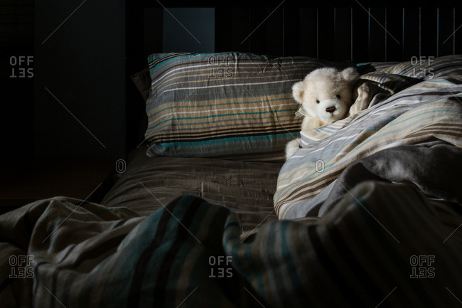 Unmade bed with stuffed teddy bear