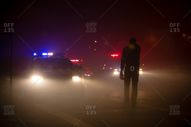Man standing in haze in front of police cars at night