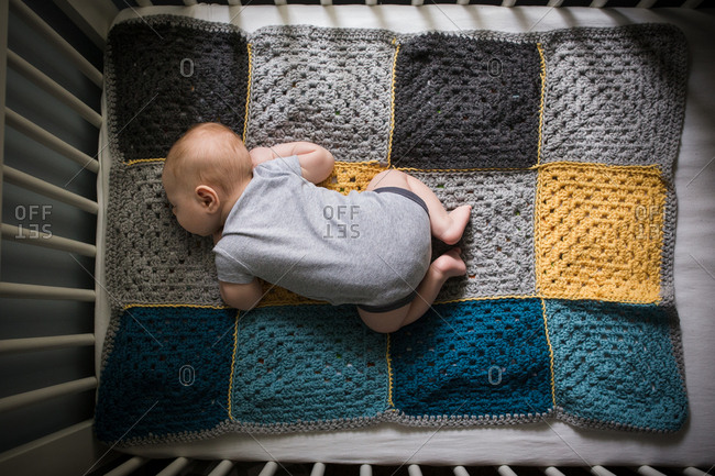 Overhead view of baby sleeping in crib on a crocheted blanket