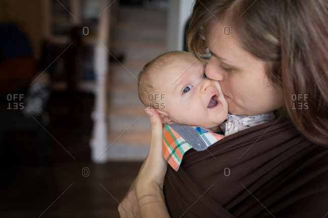 Mother holding baby in wrap carrier
