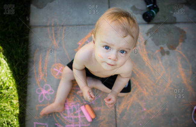 Overhead view of baby drawing with sidewalk chalk
