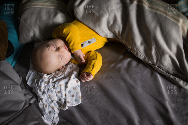 Overhead view of baby sleeping on bed