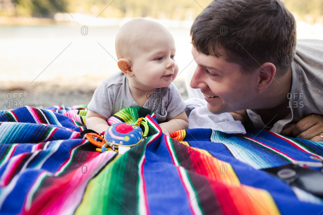 Father and baby on colorful blanket on a beach