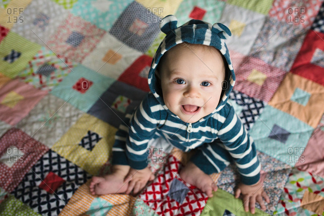 Happy baby on a colorful quilt wearing bear romper