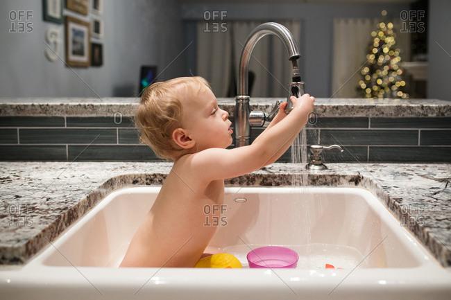 Baby bathing in kitchen sink