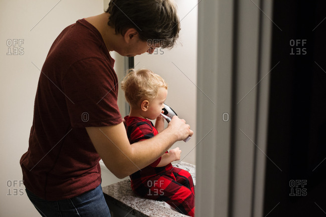 Father brushing toddlers teeth in bathroom sink