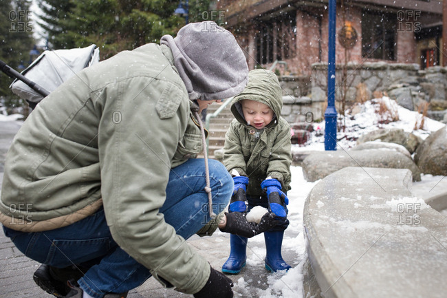 Father and toddler son making snowballs