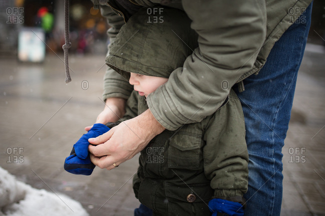 Father helping toddler son put on mittens