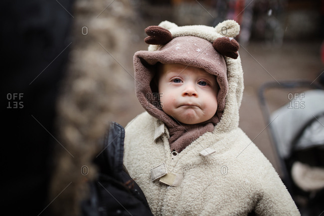 Baby in reindeer outfit outside in snow