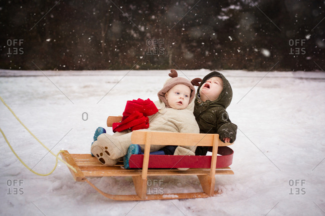Baby and toddler riding in sled in the snow