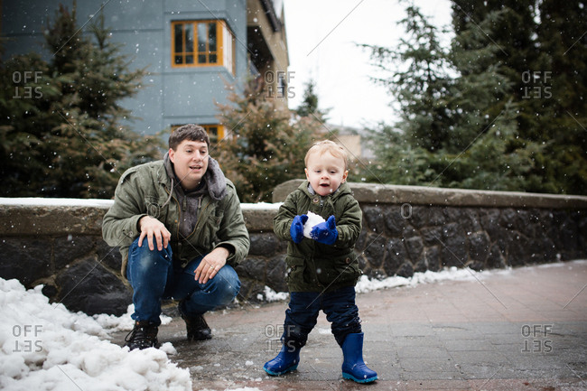 Father and toddler son making snowballs outside