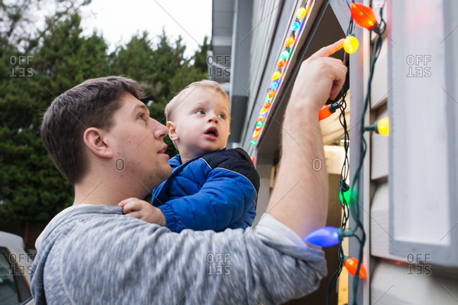 Father holding toddler and putting up Christmas lights