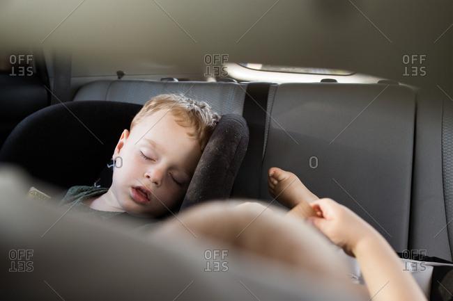Young boys sleeping in car seats
