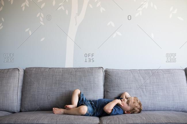 Toddler lying on living room sofa for nap