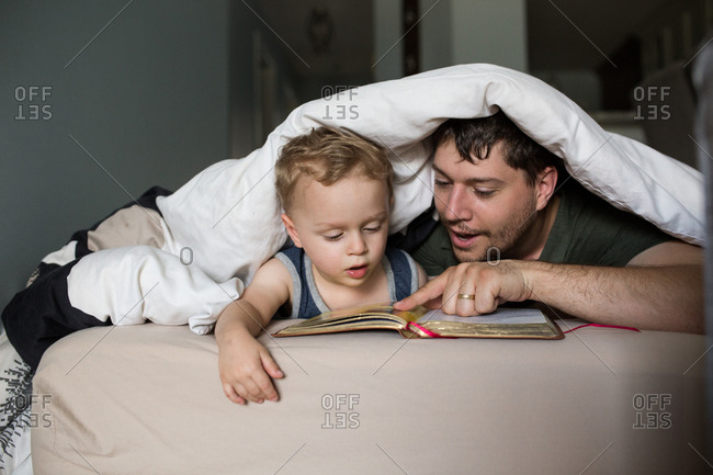 Father reading toddler son a bedtime story