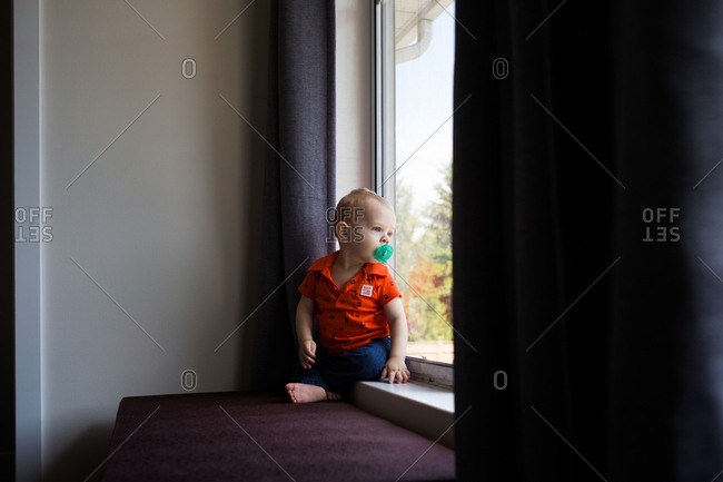 Baby boy sucking on soother looking out window
