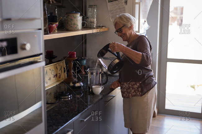 Senior woman smiling while making coffee in kitchen at home