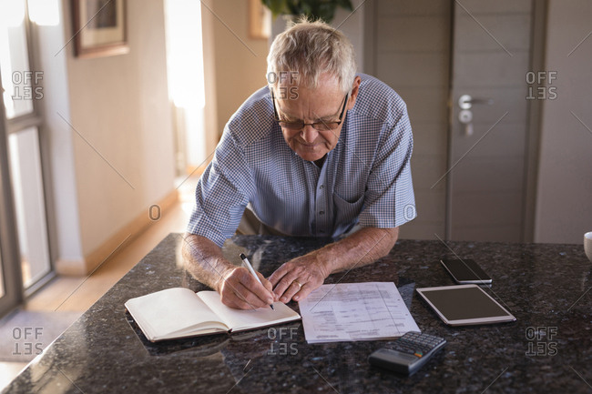 Active senior man writing on a diary at home