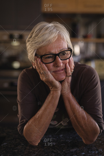 Thoughtful senior woman in kitchen at home