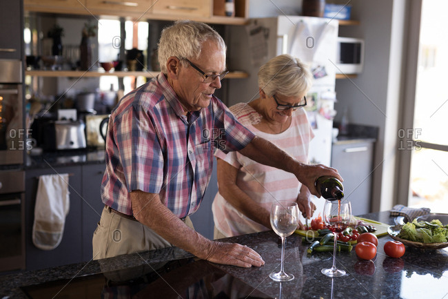 Senior man pouring wine into wine glass at home