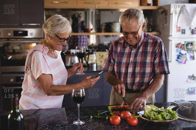 Senior couple cutting vegetables in kitchen at home