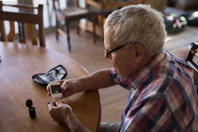 Senior man checking his blood sugar with glucometer at home