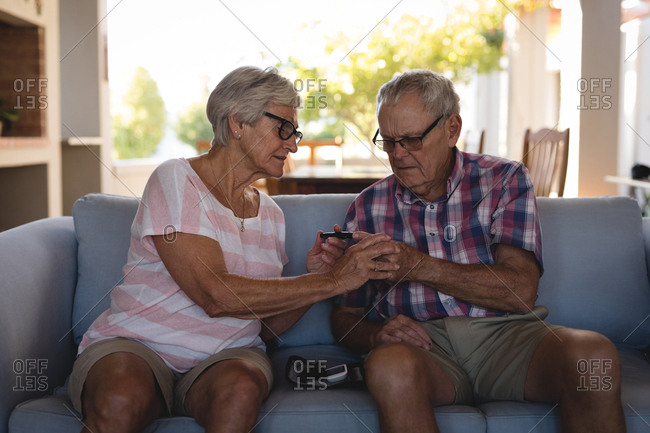 Senior couple checking blood sugar with glucometer at home