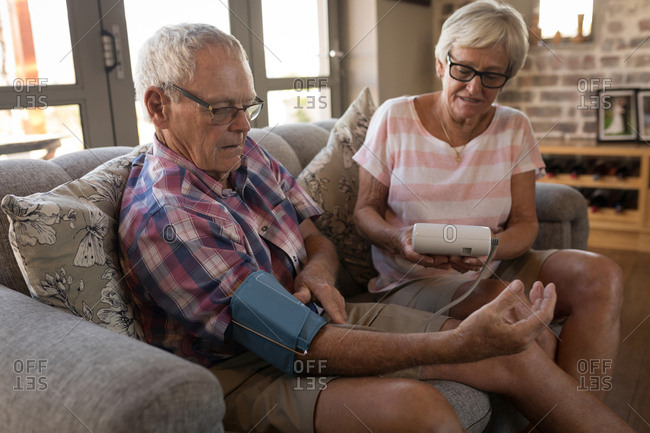 Senior couple checking blood pressure with sphygmomanometer in living room at home