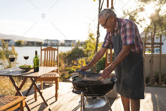 Senior man cooking fish on barbeque in the backyard