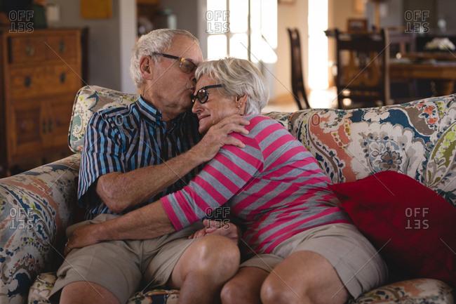 Romanced senior couple sitting on sofa at home
