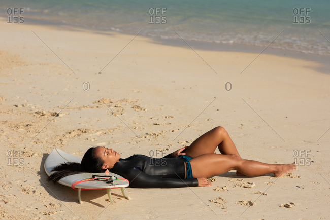 Woman sleeping on surfboard in the beach on a sunny day