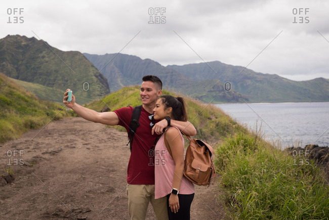 Romantic couple taking selfie with mobile phone in countryside