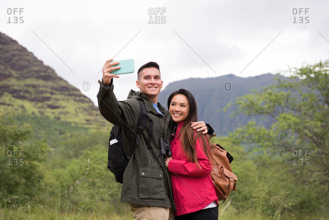 Happy couple taking selfie with mobile phone in countryside