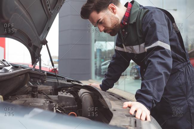 Male mechanic servicing car at repair garage