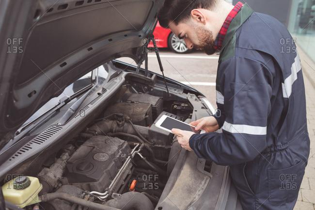Male mechanic using digital tablet at repair garage