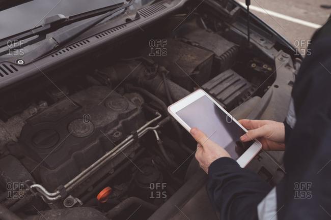 Mid section of mechanic using digital tablet at repair garage