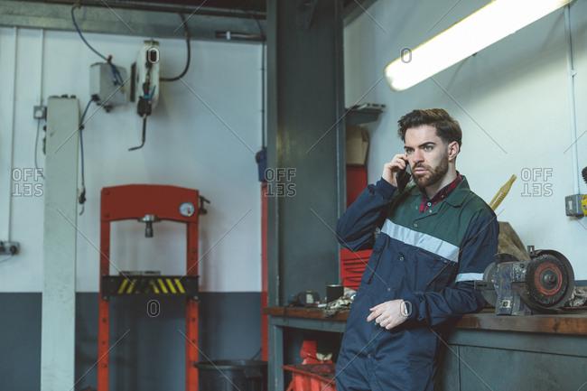 Mechanic talking on mobile phone in repair garage