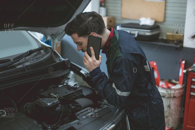 Mechanic talking on a mobile phone while examining car in repair garage