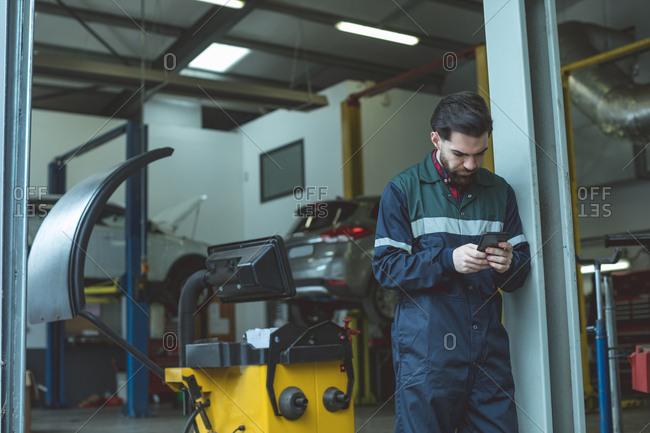 Mechanic using mobile phone in repair garage