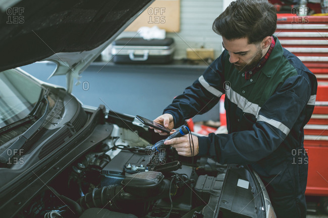 Mechanic taking picture of car engine with mobile phone in repair garage