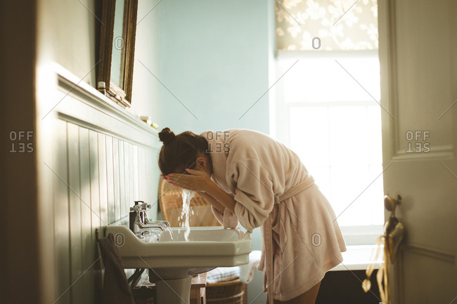 Woman washing her face in bathroom at home