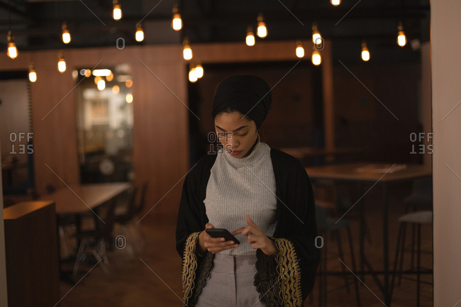 Businesswoman in hijab using mobile phone at office cafeteria