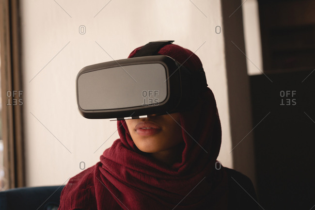 Businesswoman in hijab using virtual reality headset at office cafeteria