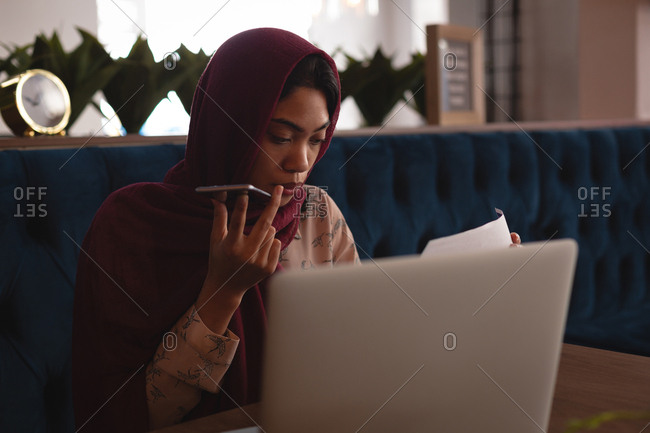 Businesswoman in hijab talking on mobile phone at office cafeteria