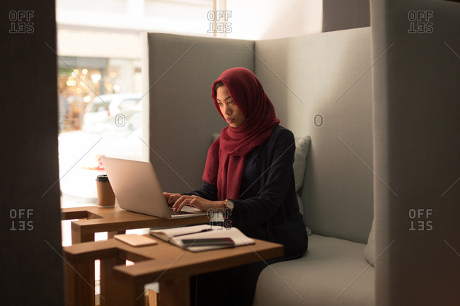 Businesswoman in hijab using laptop at office cafeteria