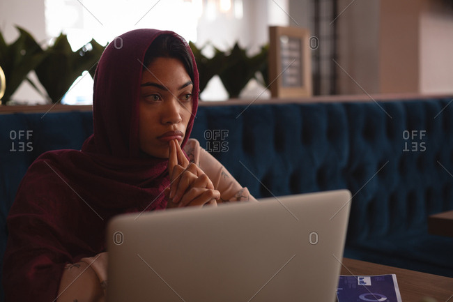 Thoughtful businesswoman in hijab relaxing at cafeteria