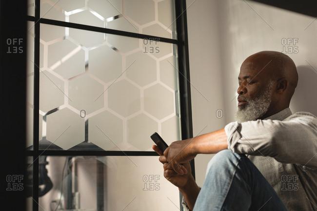 Senior graphic designer using mobile phone in office