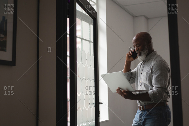 Senior graphic designer using laptop while talking on mobile phone in office