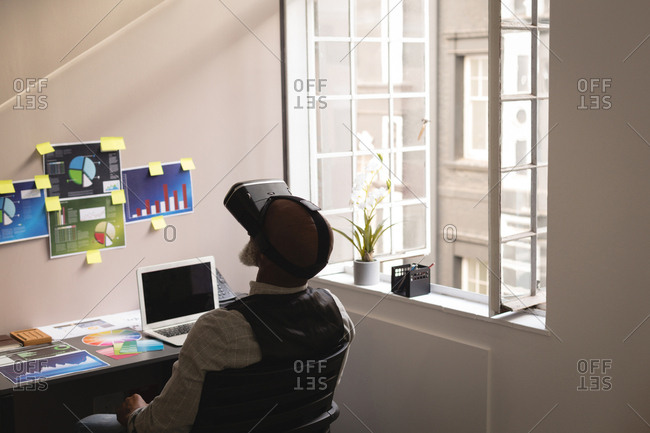 Senior graphic designer using virtual reality headset in office
